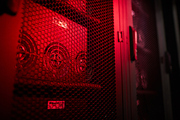 Modern powerful server equipped with video cards in ventilation cabinets at mining farm, red light