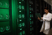 Serious busy female server technician in lab coat using laptop while testing new hardware in room with mining rigs in cabinets