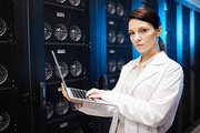 Portrait of serious confident female data server technician in lab coat standing against cabinets with video cards and using laptop