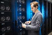 Serious busy young male technical specialist of database center standing in modern server room and checking setups on laptop