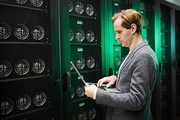Serious concentrated young IT engineer in jacket using modern laptop while doing cryptocurrency mining in server room