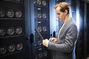 Thoughtful handsome young man in jacket standing in server room of mining farm and using laptop while updating block chain