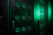 Crypto mining data center equipped with graphic cards and hardware, green light in room, copy space