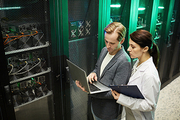 Serious busy team of IT specialists standing in server room and testing bitcoin mining hardware using laptop