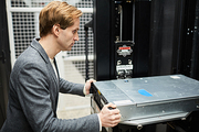 Serious handsome young man in gray jacket installing powerful hard drive into supercomputer while working in storage room of mining farm