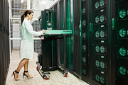 Serious attractive young woman in lab coat inserting hardware into supercomputer while working in storage room of mining farm
