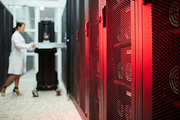 Close-up of GPU mining rig system used for bitcoin mining in storage room, technician examining hardware in background