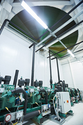 Background image of ventilation system with powerful rotating fan above hanging lamps in mining farm storage room