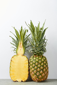 whole and half of ripe pineapples isolated on white