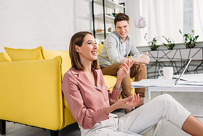 beautiful woman throwing in air baseball and sitting on floor near cheerful boyfriend sitting on sofa