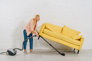 Full length view of senior woman with vacuum cleaner cleaning floor under yellow sofa