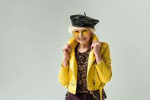 stylish senior lady posing in yellow jacket and leather beret, isolated on grey