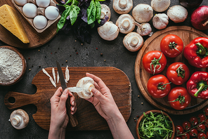 cropped shot of woman preparing ingredients for pizza on concrete table