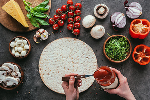 cropped shot of woman spreading ketchup onto raw pizza dough on concrete table