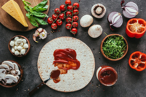 top view of pizza dough with poured ketchup and various vegetables on concrete table