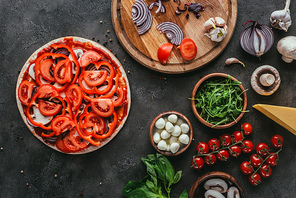 top view of uncooked pizza with different ingredients on concrete table