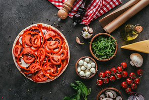 top view of uncooked pizza with various ingredients on concrete table