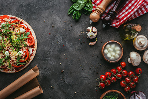 top view of uncooked pizza with ingredients on concrete table
