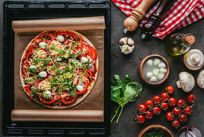 top view of freshly baked pizza with ingredients on concrete table