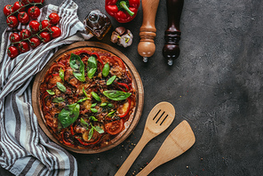 top view of pizza with wooden spatulas on concrete table