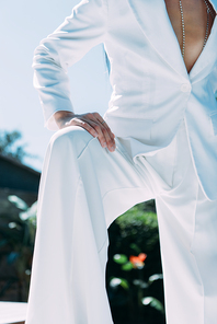 cropped view of woman in white suit posing outside