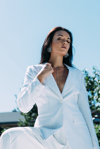 attractive woman in white suit posing and looking at camera outside