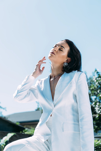 attractive woman in white suit posing with closed eyes outside