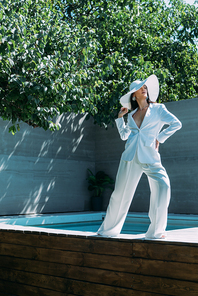 attractive woman in white suit and hat posing outside