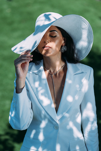 attractive woman in white suit and hat posing with closed eyes outside