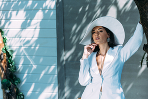 attractive woman in white suit and hat posing looking away outside