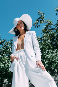 low angle view of attractive woman in white suit and hat posing outside
