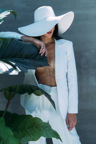 woman in white suit and hat posing and holding leave outside