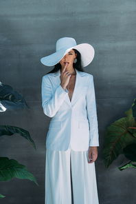 attractive woman in white suit and hat posing and obscuring face outside