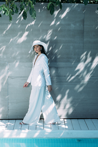 attractive woman in white suit and hat walking and looking at camera outside