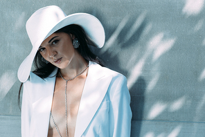 attractive woman in white suit and hat posing and looking at camera outside