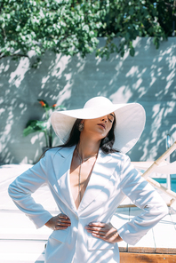 attractive woman in white suit and hat posing with hands on hips outside