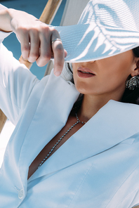 adult woman in white suit and hat posing outside