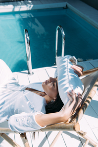 high angle view of attractive woman in white suit and hat sitting on deck chair outside