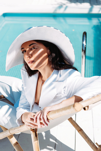 attractive woman in white suit and hat sitting on deck chair outside