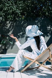 back view of woman in white suit and hat sitting on deck chair outside