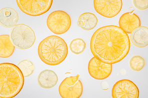 bright orange and lemon slices on grey background with water bubbles