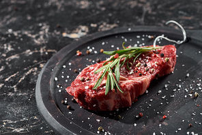 raw meat steak with rosemary twig sprinkled with salt and pepper on round wooden surface