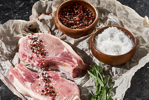 raw pork steaks on parchment paper near wooden bowls with salt and pepper on black marble surface