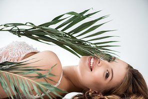 attractive girl looking at camera through palm leaf on white