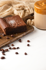 delicious brownie piece on wooden cutting board with coffee beans, coffee and cloth on white background