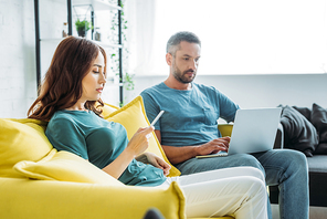 attractive woman with smartphone sitting near husband using laptop at home