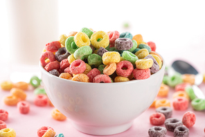 selective focus of bright multicolored breakfast cereal in bowl near glass of milk and spoon on pink background