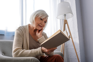 positive senior woman smiling while sitting in armchair and reading book