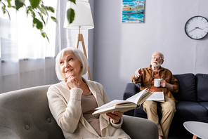 senior man pointing with finger while smiling wife holding book and looking away