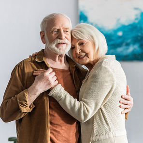 happy senior couple smiling while dancing at home